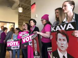 People hold signs of U.S. Supreme Court nominee Brett Kavanaugh at a rally and news conference Thursday, Sept. 20, 2018, at a Planned Parenthood office in Portland, Ore.