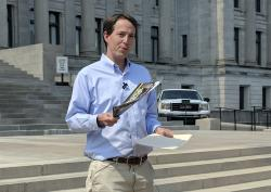 Democratic Congressional candidate Clarke Tucker shows immigration attack mailers from Republican Sen. Tom Cotton's PAC on Thursday, Sept. 20, 2018, in Little Rock, Ark.