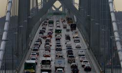 In this Dec. 10, 2015 file photo, vehicles make their way westbound on Interstate 80 across the San Francisco-Oakland Bay Bridge as seen from Treasure Island in San Francisco