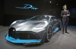 President of Bugatti Automobiles S.A.S. Stephan Winkelmann gestures as he speaks next to a 5 million euro (5.8 $) Bugatti Divo during a media presentation on the eve of Paris Auto Show in Paris, Monday, Oct. 1, 2018