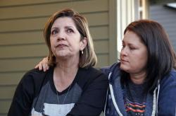 In this photo taken Monday, Sept. 24, 2018, Las Vegas shooting survivor Chris Gilman, right, puts her arm across her wife as tears well in Aliza Correa's eyes as they talk about the shooting a year earlier at their home in Bonney Lake, Wash.