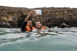 Tourists take a selfie in the water with sea lions in the background on the Palomino Islands off the coast of Lima, Peru.