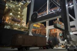 In this July, 5, 2018 photo, a post-Panamax crane loads a 40-foot shipping container onto a container ship at the Port of Savannah in Savannah, Ga.