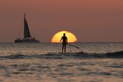 In this Dec. 31, 2013, file photo, a paddleboarder looks our over the Pacific Ocean as the sun sets off of Waikiki Beach, in Honolulu
