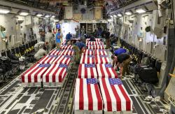 In this Sept. 13, 2018 photo, flag-draped transfer cases containing remains of unidentified service members sit inside a C-17 Globemaster plane after arriving at Offutt AFB in Bellevue, Neb.