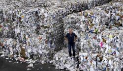 In this Thursday, Sept. 6, 2018, photo, Ben Harvey, an owner at EL Harvey & Sons, a waste and recycling company, poses on bundles of residential mixed fiber, comprised of a variety of paper and cardboard, in Westborough, Mass.