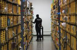 In this Dec. 21, 2016, file photo an employee of Amazon PrimeNow stacks shelves for customers making last minute holiday orders at a distribution hub in New York