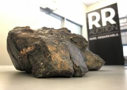 A 12-pound (5.5 kilogram) lunar meteorite discovered in Northwest Africa in 2017 rests on a table, in Amherst, N.H.