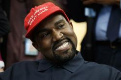 Kanye West smiles as he listens to a question from a reporter during a meeting in the Oval Office of the White House with President Donald Trump.