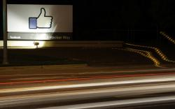 "In this June 7, 2013, file photo, the Facebook ""like"" symbol is on display on a sign outside the company's headquarters in Menlo Park, Calif. Facebook says it has purged more than 800 U.S. pages and accounts for spamming users with garbage links and clickbait"
