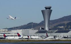 The air traffic control tower is in sight as a plane takes off from San Francisco International Airport in San Francisco.