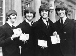 The Beatles, from left: Ringo Starr, John Lennon, Paul McCartney and George Harrison smile as they display the Member of The Order of The British Empire medals presented to them by Queen Elizabeth II in a ceremony in Buckingham Palace in London, England.