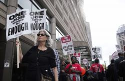 In this Tuesday, Oct. 9, 2018 photo striking hotel workers carry picket signs outside The Westin Copley Place hotel, in Boston