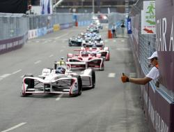 In this Sunday, July 15, 2018 file photo, a Formula E safety worker, right, gives a thumbs-up to drivers during the second of two auto races in the Formula E championship, in the Brooklyn borough of New York