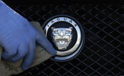In this file photo taken on Wednesday, Sept. 28, 2016, a worker polishes a Jaguar logo on a car at a Jaguar dealer in London