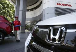 In this July 31, 2018, file photo, an employee of Honda Motor Co. cleans a Honda car displayed at its headquarters in Tokyo