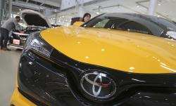 In this Nov. 13, 2017, photo, visitors take a look at Toyota cars at the automaker's showroom in Tokyo