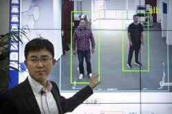 In this Oct. 31, 2018, photo, Huang Yongzhen, CEO of Watrix, demonstrates the use of his firm's gait recognition software at his company's offices in Beijing