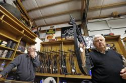 In this Oct. 20, 2017, file photo, sales clerk Tom Wallitner holds up a Mossberg 715T .22-caliber semi-automatic rifle during an auction at Johnny's Auction House, where the company handles gun sales for a half dozen police departments and the Lewis County Sheriff's Office, in Rochester, Wash.