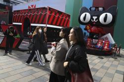 Shoppers walk by a promotion by Alibaba's Tmall online shopping platform for the upcoming 10th Singles Day event in Beijing, China