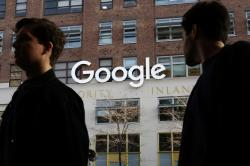In this Dec. 4, 2017 file photo, people walk by Google offices in New York