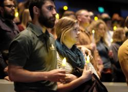 People gather to pray for the victims of the mass shooting during a candlelight vigil in Thousand Oaks , Calif.