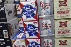 In this photo taken on Thursday, Nov. 8, 2018, cases of Pabst Blue Ribbon and Coors Light are stacked next to each other in a Milwaukee liquor store.