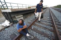 Brian Peets sits on the tracks during a visit from the outreach team including Peter Lagasse, right, at a homeless camp in New Bedford, Mass.