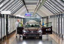In this March 5, 2018 file photo, Roland Schulz makes the final check of an e-Golf electric car in the so-called light tunnel in the German car manufacturer Volkswagen's Transparent Factory in Dresden, Germany