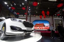 In this file photo taken Monday, April 25, 2016, visitors to Auto China 2016 stand near Zotye Auto's T300 SUV displayed in Beijing, China