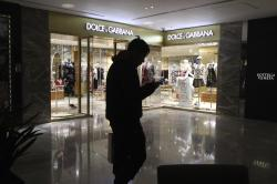 A man walks past a outlet of Dolce & Gabbana in Beijing, China, Wednesday, Nov. 21, 2018.