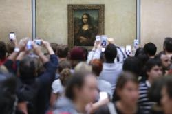 Visitors crowded in front of Leonardo da Vinci's painting 'Mona Lisa' at Musée du Louvre in Paris.