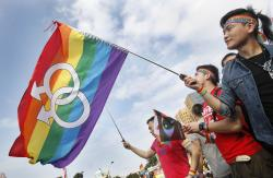 In this Dec. 10, 2016, file photo, supporters of LGBT and human rights wave rainbow flags during a rally supporting a proposal to allow same-sex marriage in Taipei, Taiwan.