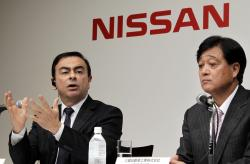 In this this Dec. 14, 2010 file photo, then Nissan Motor Co. President and CEO Carlos Ghosn, left, speaks as then Mitsubishi Motors Corp. President Osamu Masuko looks on during their joint press conference in Tokyo