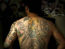 Iraqi soldier Saad Khudeir displays tattoos on his body to cover scars of the burns he was injured in a car bomb.