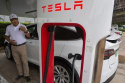 In this June 22, 2018, photo, Shan Junhua chats about privacy near his white Tesla while charging it in Shanghai