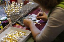 A traditional worker hand paints small blown glass beads for Christmas decorations in the village of Ponikla, Czech Republic.