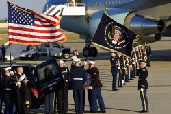 The flag-draped casket of former President George H.W. Bush is carried by a joint services military honor guard to a hearse at Andrews Air Force Base in Md.