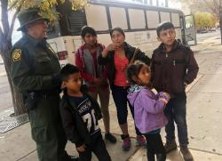 In this Thursday, Nov. 29, 2018 photo, a migrant family from Central America waits outside the Annunciation House shelter in El Paso, Texas, after a U.S. Immigration and Customs Enforcement officer drops them off