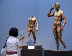 """Reporter Sookee Chung takes a photo of a sculpture titled """"Statue of a Victorious Youth, 300-100 B.C."""" at the J. Paul Getty Museum in Los Angeles."""
