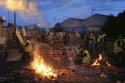 "In this Tuesday, Dec. 5, 2018 file photo, demonstrators stand at a makeshift barricade set up by the ""yellow jackets"" protesters to block the entrance of a fuel depot in Le Mans, western France."