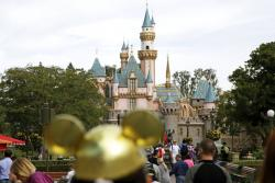 Visitors walk toward Sleeping Beauty's Castle in the background at Disneyland Resort in Anaheim, Calif.
