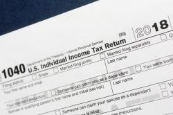 This July 24, 2018, file photo shows a portion of the 1040 U.S. Individual Income Tax Return form for 2018 in New York. The Child Tax Credit changed considerably in 2018