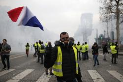 A demonstrator waves a French flag on the Champs-Elysees avenue Saturday, Dec. 8, 2018 in Paris