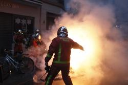 Firefighters try to extinguished a car set on fire by demonstrators during clashes with riot police, in Paris, France, Saturday, Dec. 8, 2018