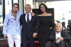Honoree and actor Michael Douglas, second left, poses with his father actor Kirk Douglas, from right, wife Catherine Zeta-Jones and son Cameron Douglas following a ceremony honoring him with a star on the Hollywood Walk of Fame in Los Angeles.