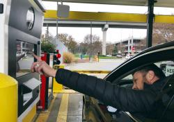 In this Friday, Dec. 7, 2018, photo, a rental car driver demonstrates a new biometric scanning machine by placing his finger on the reader at the Hertz facility at Hartsfield-Jackson Atlanta International Airport, in Atlanta
