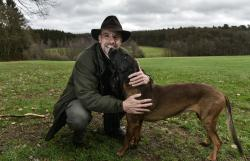 In this Dec. 7, 2018 photo Dirk Gratzel poses for a photo with his dog at his hunting ground in Stollberg, Germany.