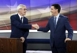 In this Oct. 19, 2018, file photo, Democratic challenger Tony Evers, left, and Wisconsin Gov. Scott Walker, a Republican, shake hands during gubernatorial debate in Madison, Wis.