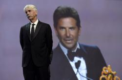 "Sam Elliott looks on as Bradley Cooper, seen in background screen, accepts the director of the year award for ""A Star Is Born"" at the 30th annual Palm Springs International Film Festival."